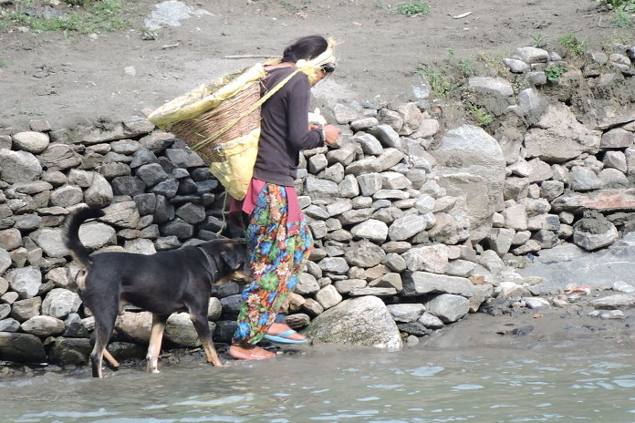 A girl in Kullu walks by River Beas